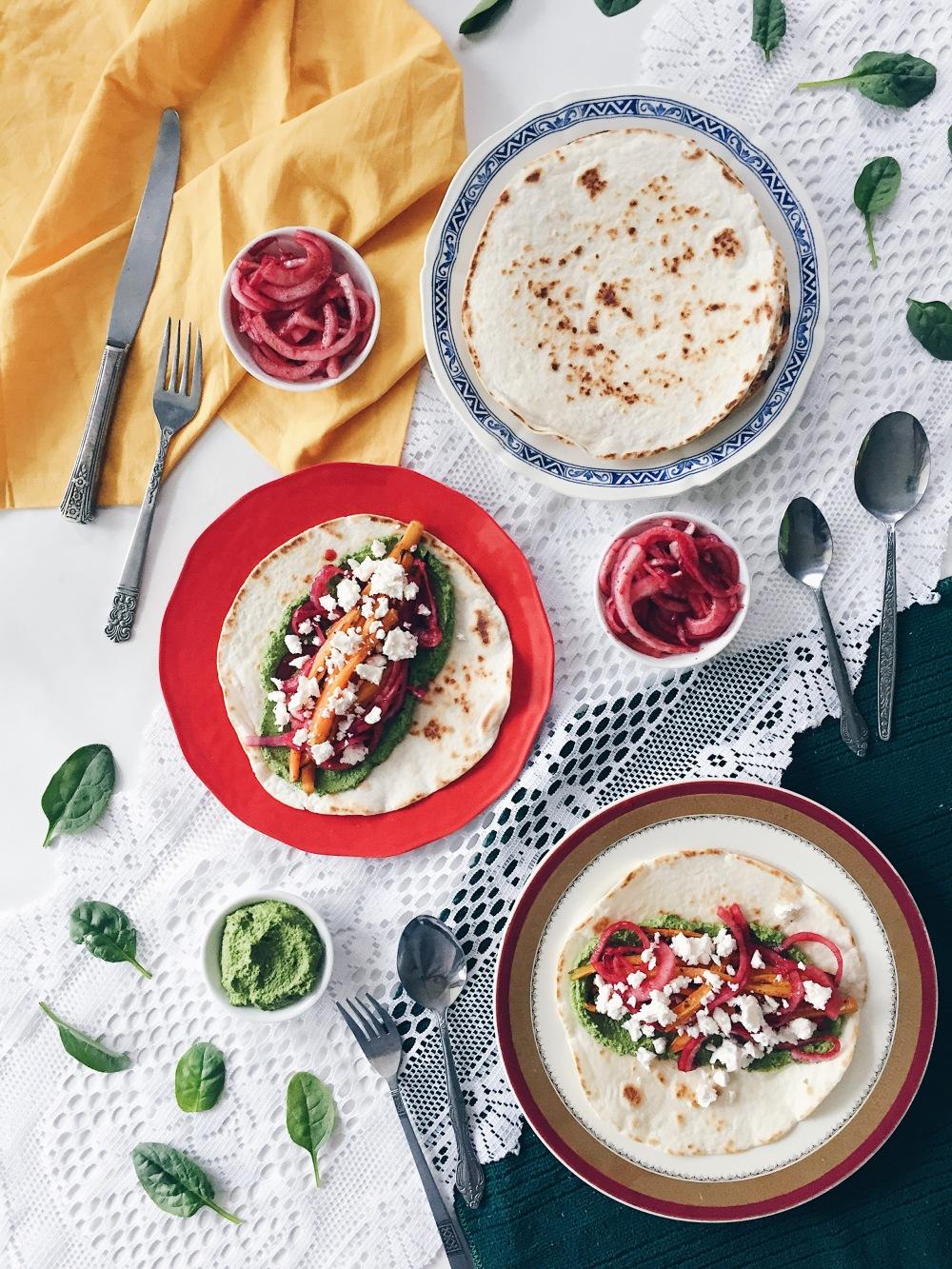 Tacos aux carottes rôties, pesto d'épinards et graines de citrouille, feta, menthe, oignons marinés et crème sûre