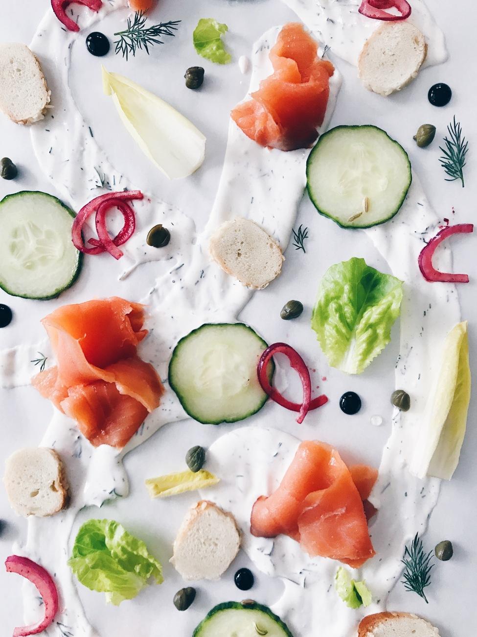 Entrée servie sur la table : saumon fumé, fromage à la crème, légumes marinés et bagel
